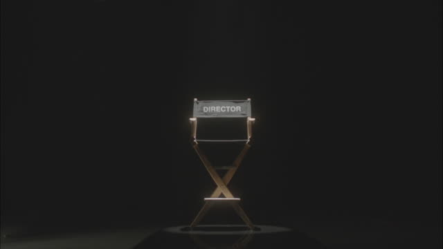 vídeos de stock, filmes e b-roll de spotlight on directors chair - estúdio de cinema
