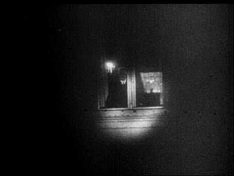 b/w 1933 spotlight on man standing in window at night - one mature man only stock videos & royalty-free footage