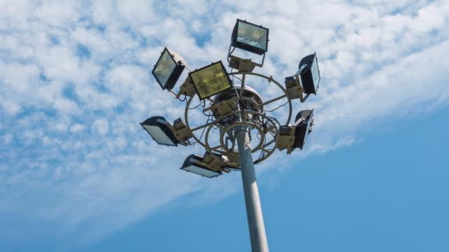 vídeos de stock e filmes b-roll de destaque, luzes do estádio, com céu azul 4 k timelapse - iluminado por holofote