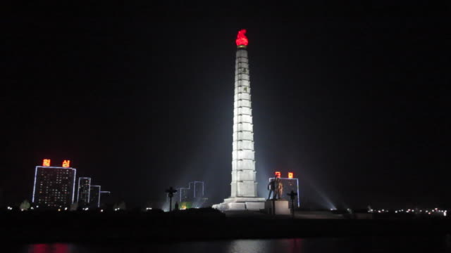 spotlights illuminate the tower of juche at night in pyongyang. - pyongyang stock videos and b-roll footage