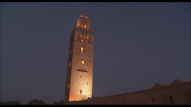 vídeos de stock, filmes e b-roll de spotlights illuminate the tower of the koutoubia mosque. - mesquita