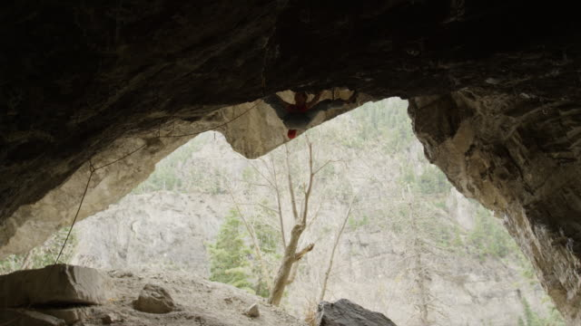 spotter watching woman rock climbing on ceiling of cave / american fork canyon, utah, united states - american fork canyon stock videos & royalty-free footage