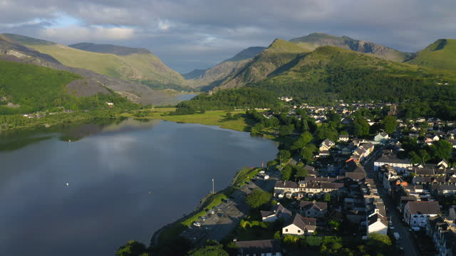 sprawling lush green landscape and a provincial village in snowdonia wales uk - aerial shot - snowdonia stock videos & royalty-free footage