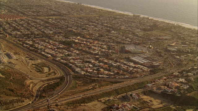 stockvideo's en b-roll-footage met aerial sprawling residential area near the coast, with white line of surf beyond houses - breedbeeldformaat