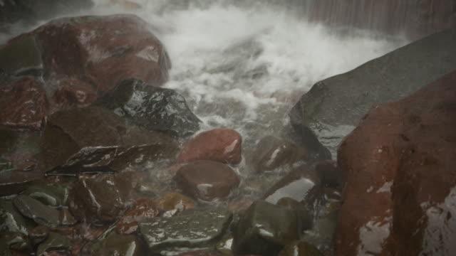 Spray from the Kaaterskill Falls gathers around varied rocks, Catskill Mountains, New York State, USA.