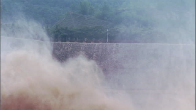 spray from water plume obscures wall of xioalangdi dam - hydroelectric power stock videos and b-roll footage