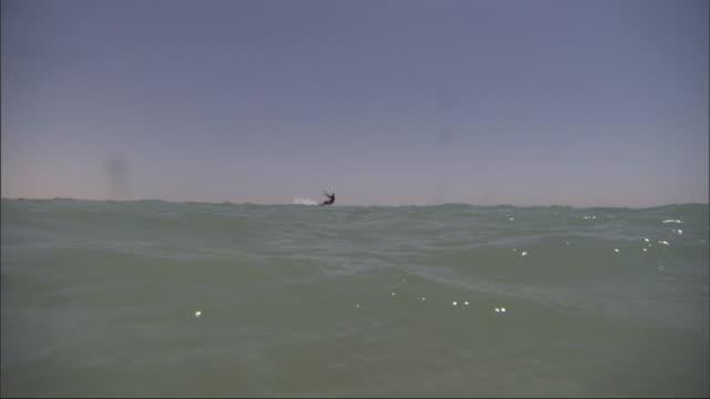 vidéos et rushes de spray hits the camera lens as a kitesurfer sails by under his parachute. - harnais de sécurité