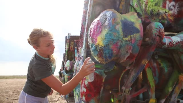 spray painting the cadillacs at cadillac ranch - installationskunst stock-videos und b-roll-filmmaterial
