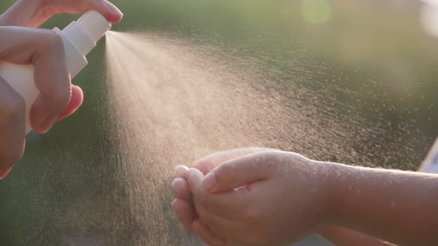 vídeos y material grabado en eventos de stock de slo mo spraying solución antiséptica en las manos de los niños - botella
