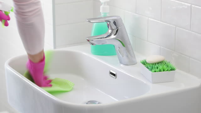 spraying disinfectant and scrubbing bathroom sink with rag - washing up glove stock videos & royalty-free footage