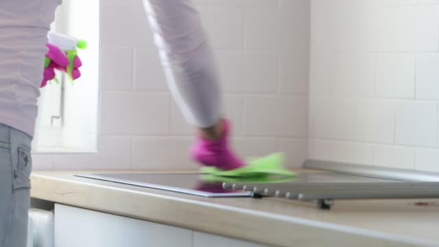 sprühen des infektierstums auf die herdplatte und wischen mit lappen - lappen reinigungsgeräte stock-videos und b-roll-filmmaterial