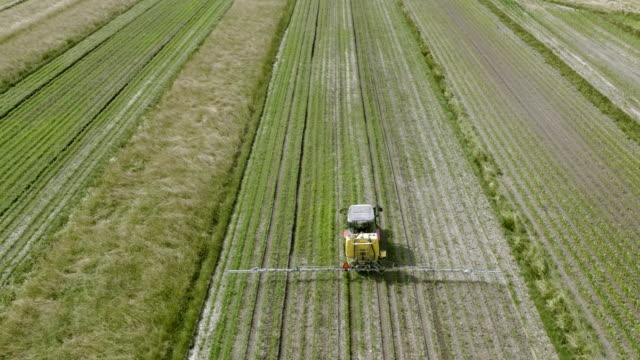 トラクターでフィールドの作物を溶射航空 - トラクター点の映像素材/bロール