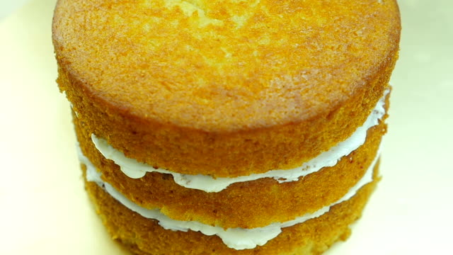 Spread butter cream on cake. Front view. Close up. Slow motion.