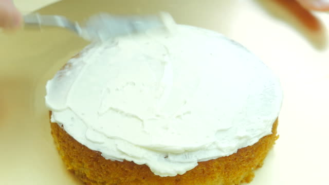 Spread butter cream on cake. Front view. Close up.