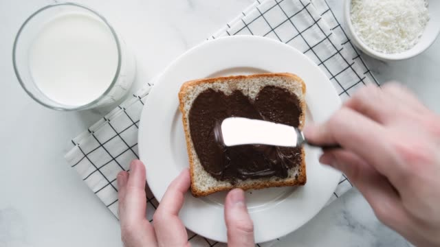vídeos y material grabado en eventos de stock de spread chocolate nut butter on toast - enfoque de objetos sobre la mesa
