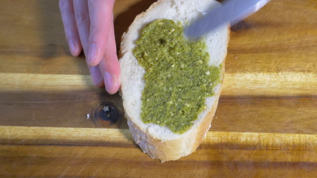 spread green pesto on bread