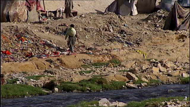 spread of polio to neighbouring countries children searching amongst debris under flyover debris rubbish and makeshift tents alongside small river in... - polio stock videos & royalty-free footage