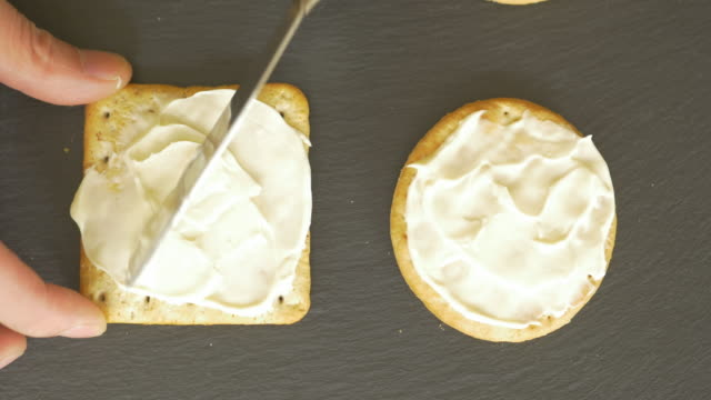 spread soft cheese on biscuit crackers - appetizer stock videos & royalty-free footage