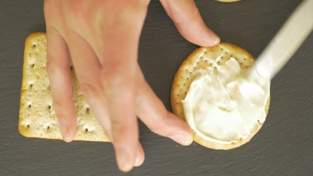 spread soft cheese on biscuit crackers - slate rock stock videos and b-roll footage