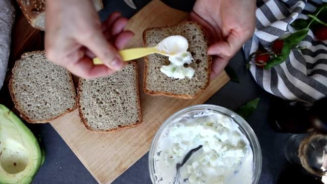 verspreiding van avocado en zure room saus op brood