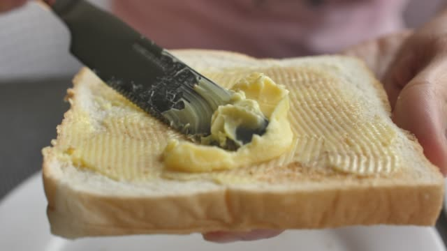 spreading butter on a slice of bread - butter stock videos & royalty-free footage