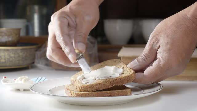 spargere burro su una fetta di pane - formaggio video stock e b–roll