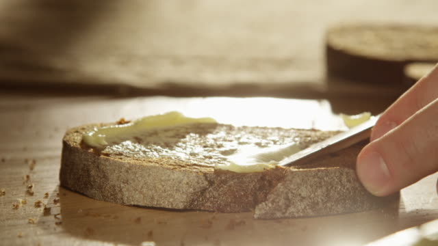spreading butter on fresh artisan rye bread slice with a knife close up of a palm on a wooden table with sunshine and sun flares shot on red epic - bread stock videos & royalty-free footage