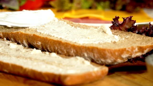 サンドイッチパンにクリームチーズを広げる - クローズアップ - サンドイッチ作り点の映像素材/bロール