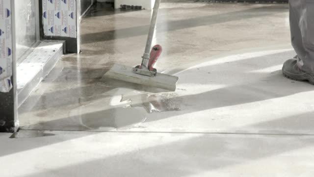 spreading even liquid resin layer on cement floor - sigillante video stock e b–roll