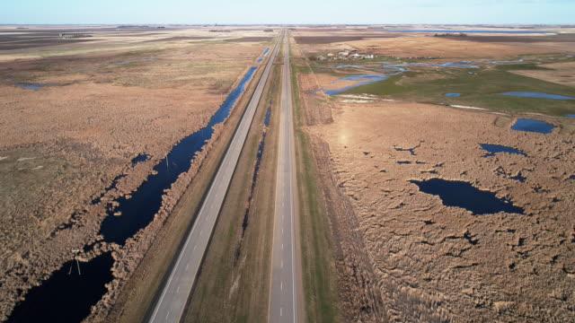 vidéos et rushes de inondation printanière autour de l'autoroute 2 dans les champs du dakota du nord au printemps. vidéo drone aérien avec le mouvement de la caméra arrière. - dakota du nord