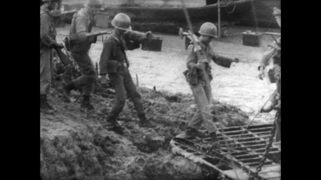 Spring time in Vietnam / CU damaged army trucks from Viet Cong ambush / soldiers crossing river path carrying guns and supplies / soldiers wading...