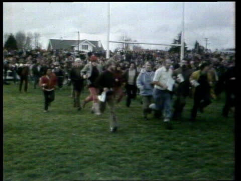 stockvideo's en b-roll-footage met springboks tour of new zealand itn lib hamilton bv crowd through fence ms rush onto pitch ts police run pull out crowd ms smoke from tear gas ms... - 1981