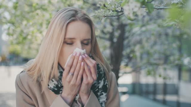 springtime allergy. woman sneezing on the city street - sneezing stock videos & royalty-free footage