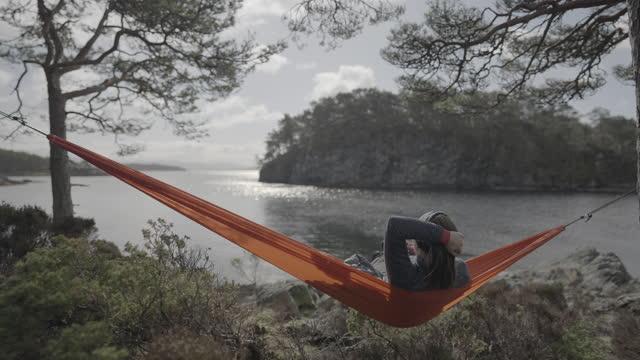 stockvideo's en b-roll-footage met lente in noorwegen: avonturen in de natuur buiten op hangmat - zonnig