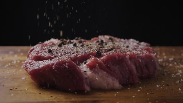 sprinkle black pepper on beef steak in slow motion - marbled effect stock videos & royalty-free footage