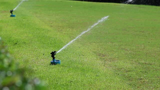 sprinkler water for grass on field.
