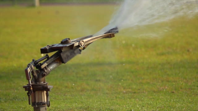 vídeos de stock, filmes e b-roll de sprinklers no futebol pitch slow motion - aspersor