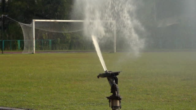 sprinklers on the football pitch slow motion - sprinkler system stock videos & royalty-free footage