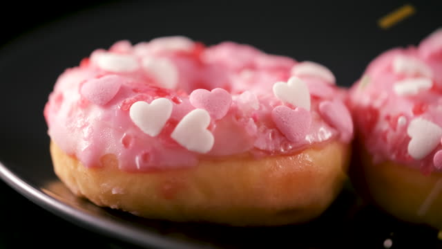 sprinkles falling onto pink donuts with heart shaped sprinkles - sliding shot - dessert stock videos & royalty-free footage