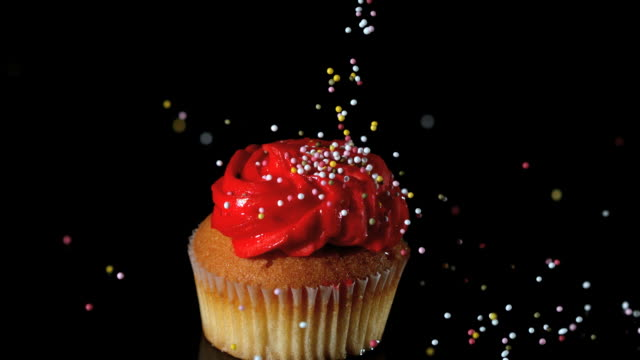 sprinkles falling onto red iced cupcake - cupcake stock videos & royalty-free footage