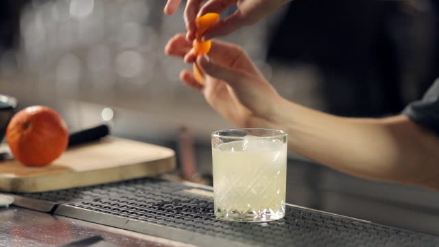 sprinkling a glass of cocktail with twisted orange peel - serving food and drinks stock videos & royalty-free footage