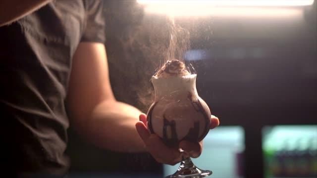 sprinkling cinnamon  over strawberry milkshake - strawberry milkshake stock videos & royalty-free footage