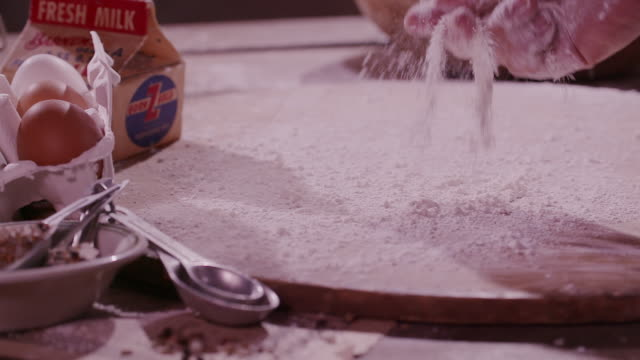 stockvideo's en b-roll-footage met sprinkling flour on a wooden board - snijplank