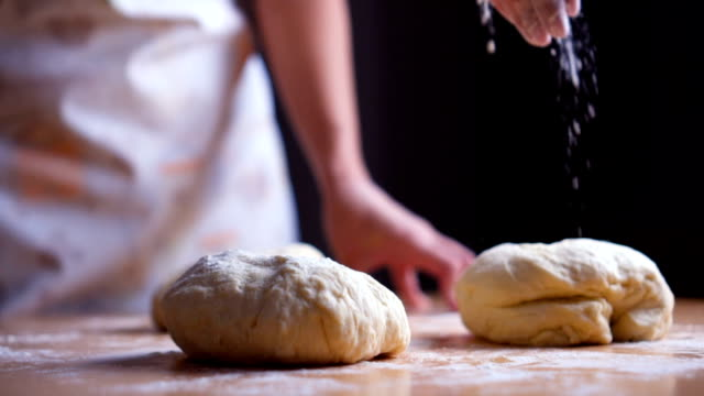 sprinkling flour over fresh dough - sprinkling stock videos and b-roll footage