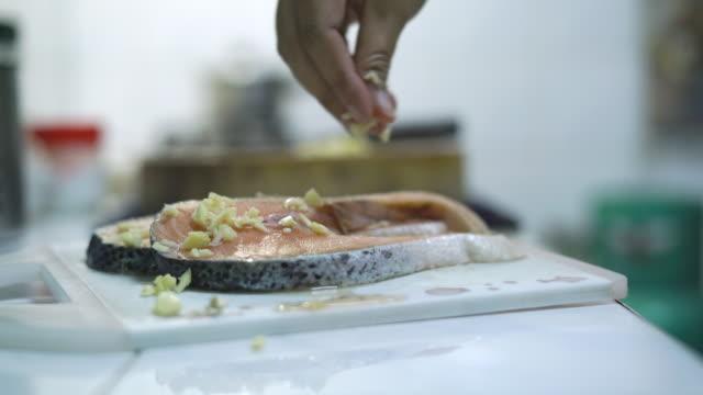 vídeos de stock e filmes b-roll de sprinkling garlic on raw salmon - filete de salmão