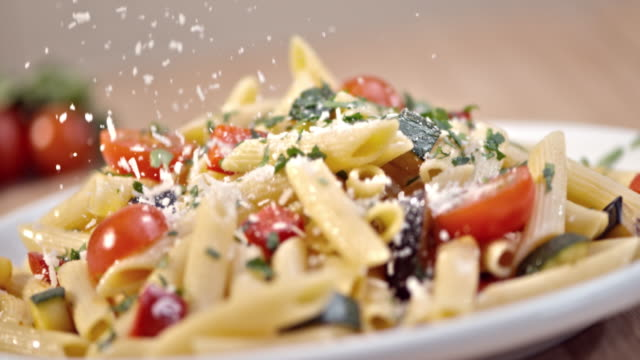 slo mo sprinkling parmesan over pasta with fresh vegetables - food stock videos & royalty-free footage