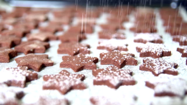 Sprinkling powdered sugar on star shaped chocolate cookies