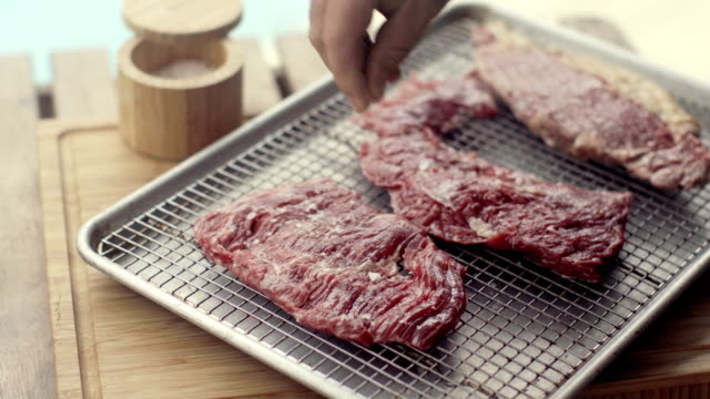 sprinkling rock salt flakes into a churrasco steak - raw food stock videos & royalty-free footage