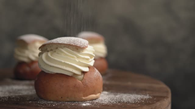 sprinkling sugar on traditional swedish semlor pastry dessert - bun bread stock videos & royalty-free footage