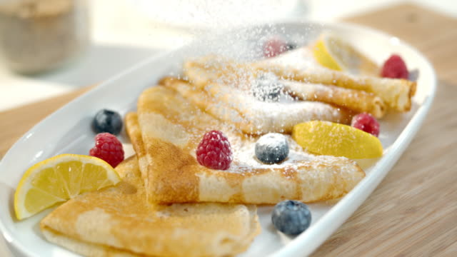 slo mo ld sprinkling sugar over crepes - pancake stock videos & royalty-free footage